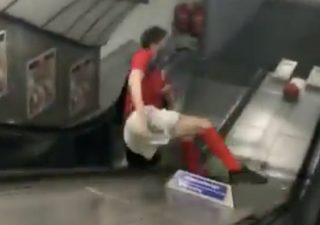 Man slides down tube escalator