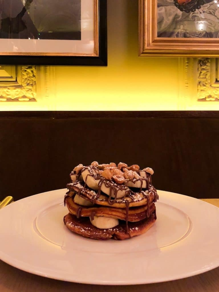 pancake stack topped with bananas and Nutella spread only to be topped with a generous layer of chopped hazelnuts